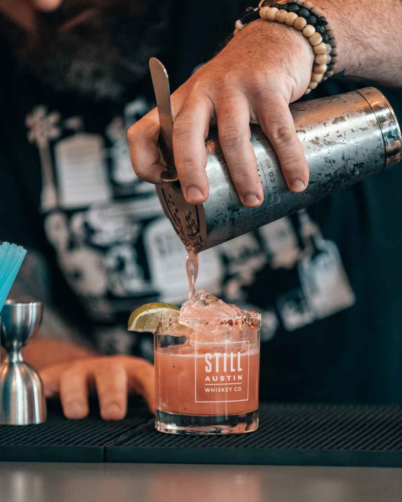 bartender pouring a cocktail at the still austin whiskey co. tasting room