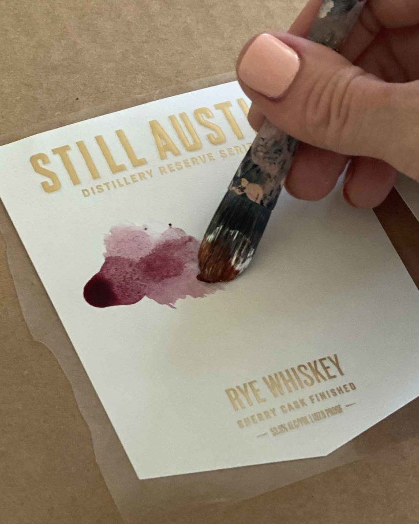 artist Rachel Dickson hand painting labels for still austin whiskey co distillers reserve series sherry cask finished rye